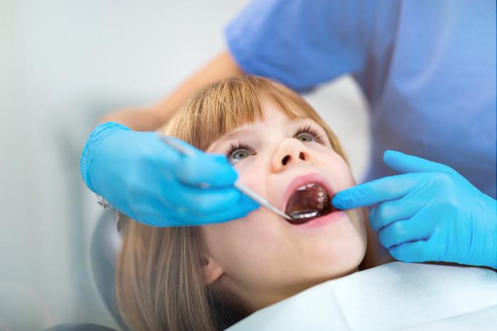 bambina sulla poltrona del dentista si sottopone a visita di odontoiatria pediatrica